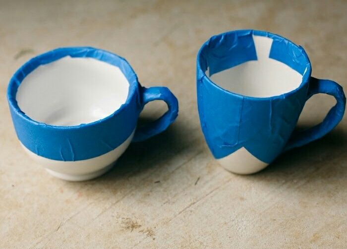1. Put the blue painters tape on the mugs leave the places that you want to spray paint uncovered.  When doing this make sure that the tape is pulled tight with no ripples, unlike the photo. if it is wrinkled, the paint will creep up underneath and you will have to clean up the line after.