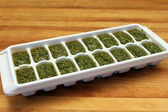 Use a spoon to fill the compartments of the tray with pesto.