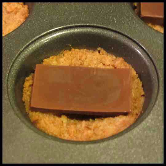 Step 3:  While the crust is in the oven, break two of the candy bars into rectangles. Remove pan from oven; place one rectangle into each cup.
