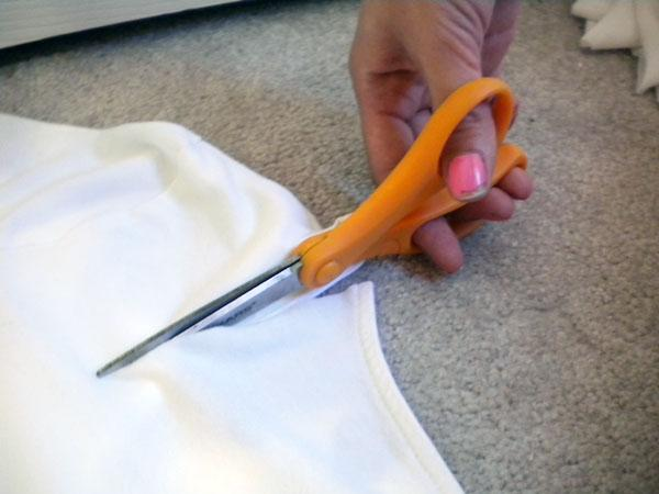 "2. Begin cutting one half of a ""U"" shape in the back. Make sure you don't cut through both sides! Try not to pull or move the shirt too much while you cut, and avoid closing the blades of the scissors all the way so you don't get jagged edges. Once you have cut half of the U shape, stop cutting."