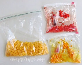 If you are coloring your cheese, put about 2 tablespoons of cheese into a zip top bag. Add a few drops of red coloring and shake to coat cheese. Repeat with yellow coloring.