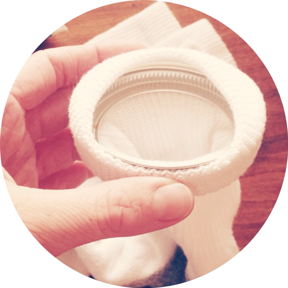You can use a mason jar lid to hold open the sock to pour in the rice.