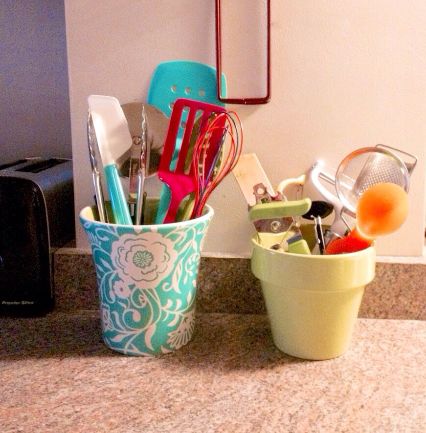 Use decorative flowerpots as utensil holders for a pop of color in the kitchen. Super cute!