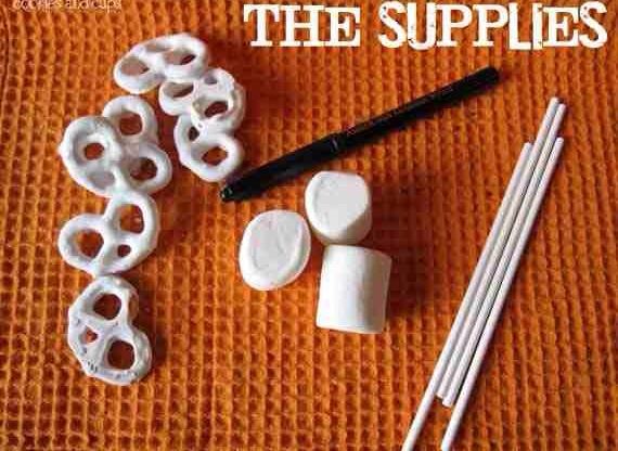 Next, assemble your supplies… -white chocolate covered pretzels -large marshmallows -lollipop sticks -food writer (or black icing)