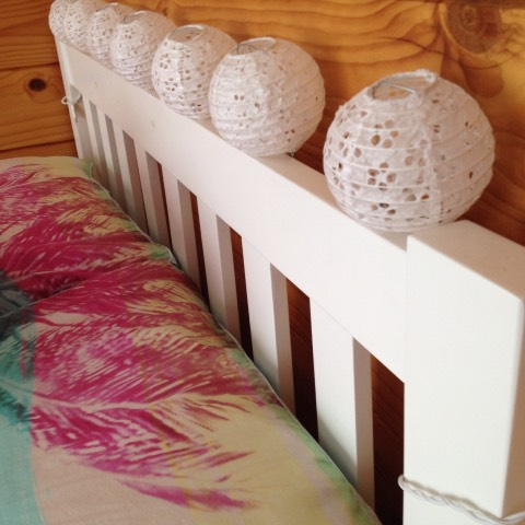 Some lanterns along the headboard of your bed can make the room cosier at night