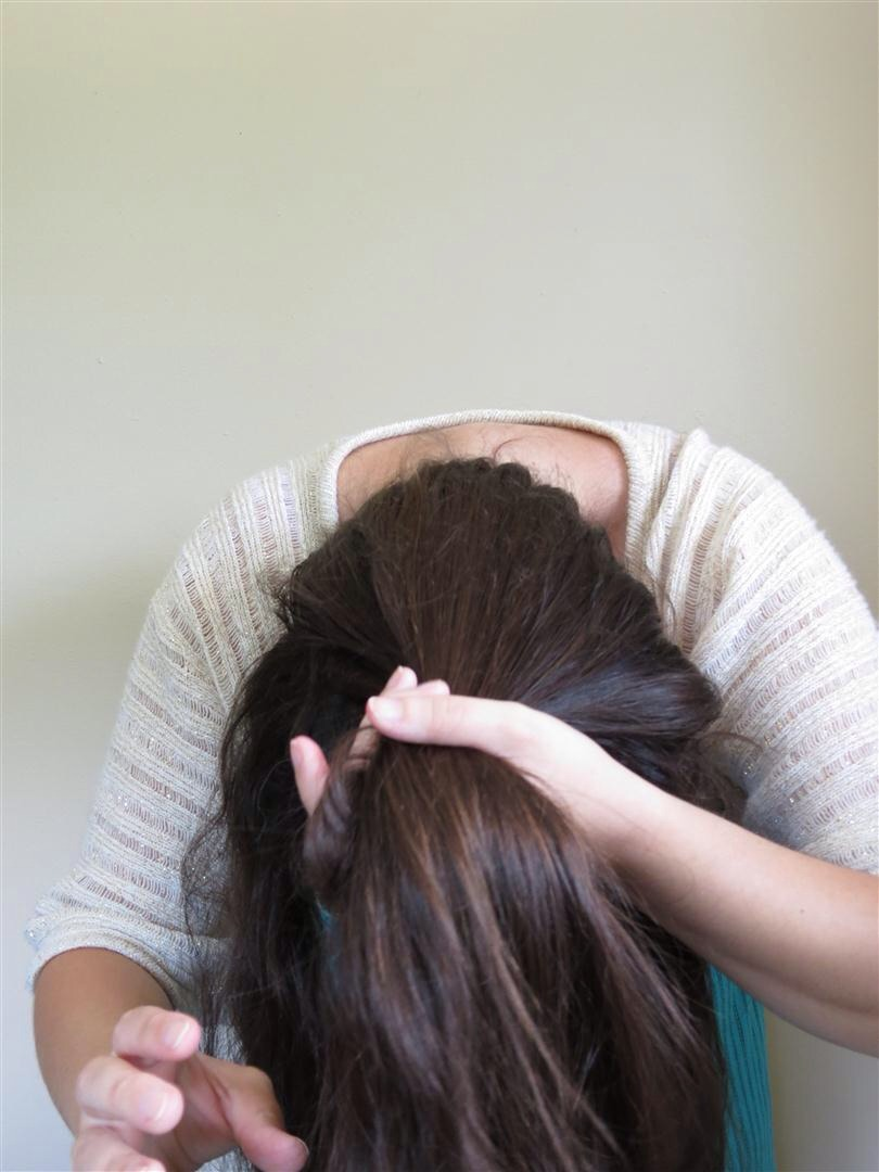 2.Flip your hair over and bend at the waist. Pull your hair through the opening of your T-shirt so that the opening stretches around your hairline.