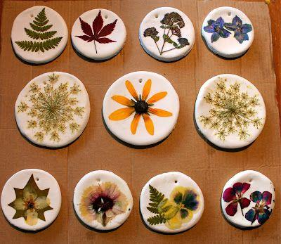 Dough is made from 1 cup baking soda, 1/2 cup corn starch, 3/4 cup of warm water. Roll flat, cut out circles, punch hanging holes, and bake at 200 degrees F for an hour. Mod podge pressed flowers onto bases and hang.