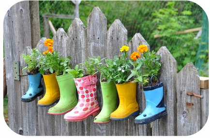 Rainboot Planters  I love this idea of using old boots as planters -- and then hanging them on the fence! A pop of color against the weathered boards looks great.