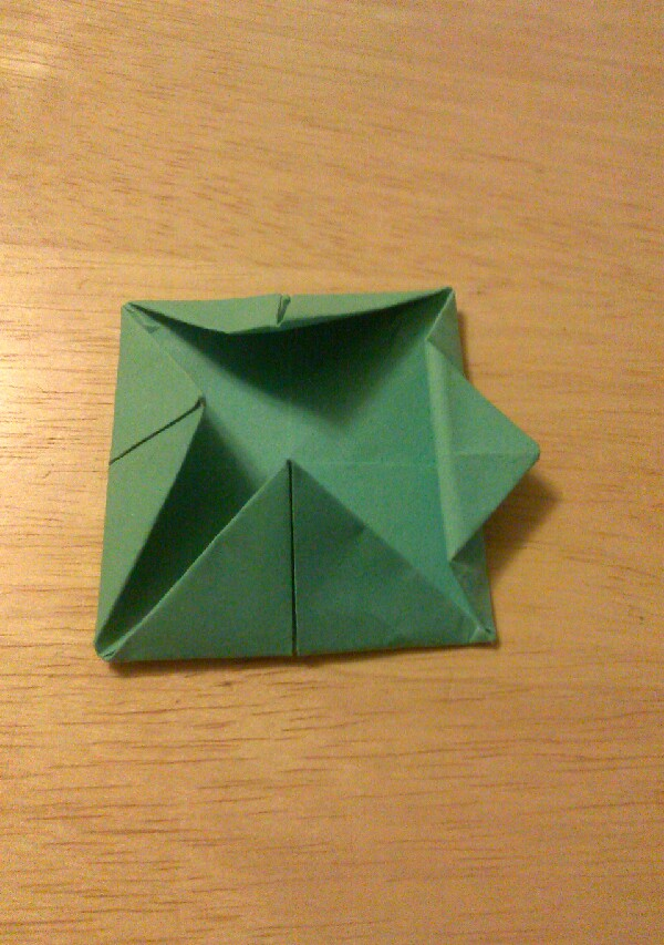 Step 5:  Fold half of a triangle till it just crosses the edge like so. Repeat on all 4