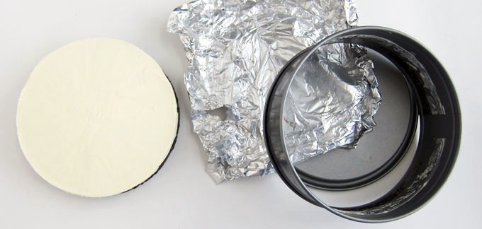 Remove cheesecake from freezer. Unlatch and remove the springform pan sides. You may need to warm up the metal sides a bit. Wet a towel with hot water, wrap around the pan, allow sides to warm slightly, unlatch and remove sides. Carefully peel off non-stick foil and set cake on a serving platter.