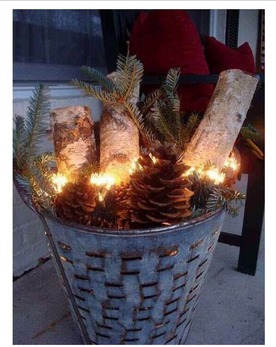 All you need is a basket, pinecones, some fake tree limbs or garland, and some lights. Hook it up at night and it looks great!