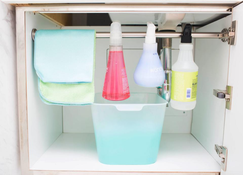 11. Install a small tension rod under your sink to hang your cleaning supplies and allow more room below for storage.