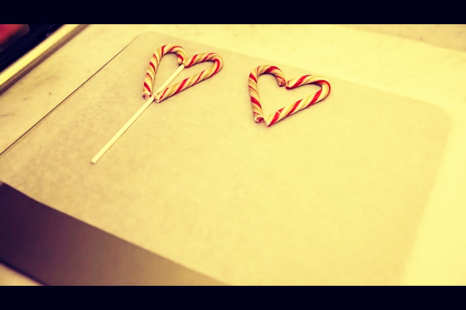 Place Popsicle stick in between the two candy canes on the parchment paper.