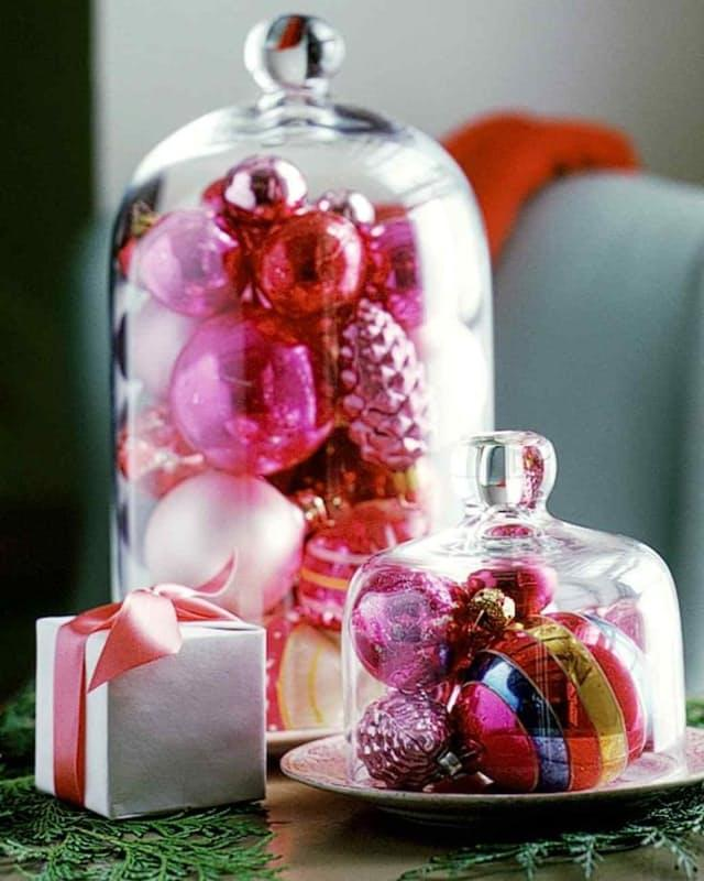 Colorful ornaments under a cloche or cake dish cover, like these fromMartha Stewart, make for instant holiday decor.