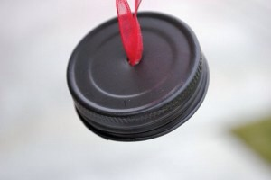 Nail a hole in the center of the jars lid. Pull the nail out and now you should have a hole in your lid. Cut a piece of ribbon about 6 inches long. Poke both ends of the ribbon through and tie a knot on the underside: