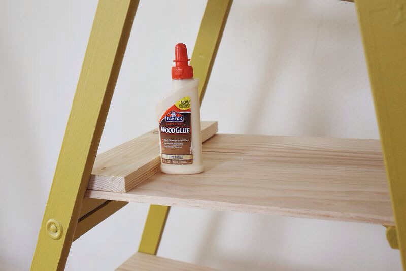 Our quick fix solution was to add a short piece of wood to the edge of the shelf planks to try and give the shelf more height. We used wood glue to secure the pieces together. In the above photo I have the shelf laying upside down while the glue dried. After the shelves were completed we painted.