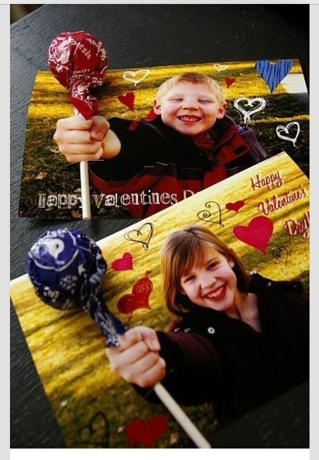 Take a picture of your kids holding out their fist. After you develop it make a hole at the top of their fist and in the bottom of their fist. Put a sucker in the top hole (top of their fist) and out through the bottom hole. It looks like they're holding out a sucker for their valentine. Great idea!