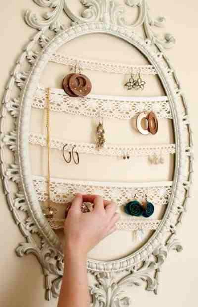 Taking a photo frame of your choice, remove the back and discard them. Glue lace trimmings on both ends. Be creative and decorate as you chose. Hang to desired area and organize your jewelry.