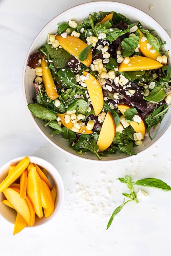 Serves: 4 Ingredients Corn – 2 ears, kernels shaved Peaches – 2, sliced Balsamic vinegar – 1½ tbs. Maple syrup – 1 tsp. Olive oil – 3 tbs. Mixed greens – ¼ lb. Sliced almonds – ¼ cup Goat cheese – for serving (~2 oz.)