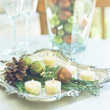 Tray chic  A fancy vintage silver tray becomes a standout centerpiece when dressed with glowing tea lights, several glitzy ornaments, fresh cedar branches and a single pinecone.