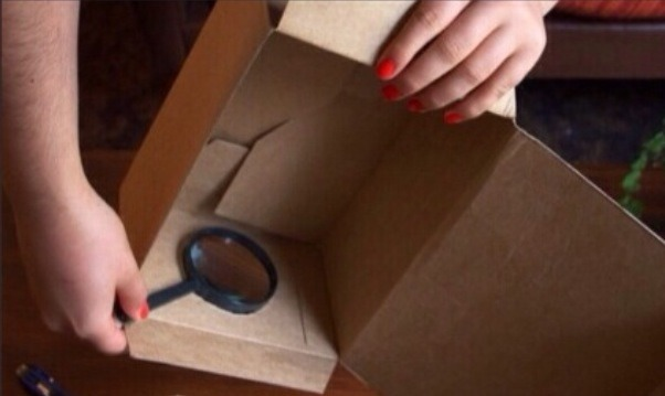 Put the magnifying glass inside the box lining up with the hole.