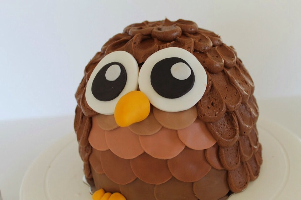 Place the eyes on first, putting them close together. Then using a toothpick inserted in the beak, place it between the eyes. Place the yellow balls in sets of three at the bottom of the cake for the feet.