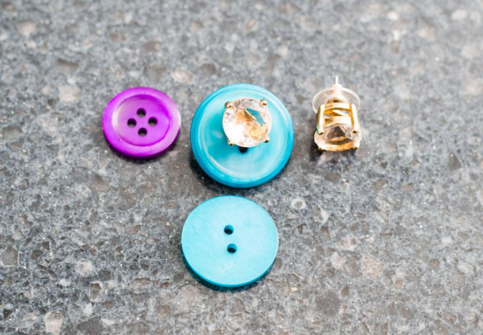 6. Secure your earrings through the holes of a button before tossing them in your bag so you don't lose one. It's not a good idea to work out in your jewelry, but if you're worried about losing them in your locker or bag, this is a great solution.