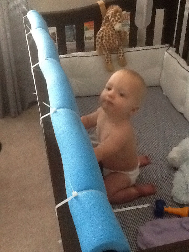 My 16month old likes to bang her head while throwing her tantrums.  Cut pool noodle down center (not completely in half just one slit) slide over rail and secure.P.S.pic is from google not my baby she's napping so I couldn't get in there to take pic of my creation but it looks better than this ;p