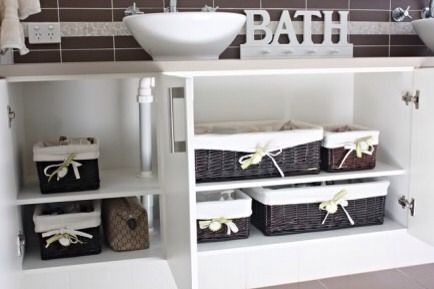 Matching Labeled Baskets Under Cabinet  Did you find a great (January) sale on storage baskets? Scoop them up, label them, and use them as attractive bathroom organizers you actually don't mind showing off!