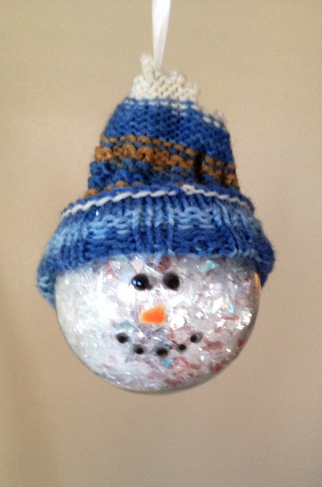 Fill a clear ornament with fake snow, cut the toe of a baby's fuzzy or crochet sock and glue onto the top, use sharpie or paint to add the eyes nose and mouth. So easy, and so adorable!