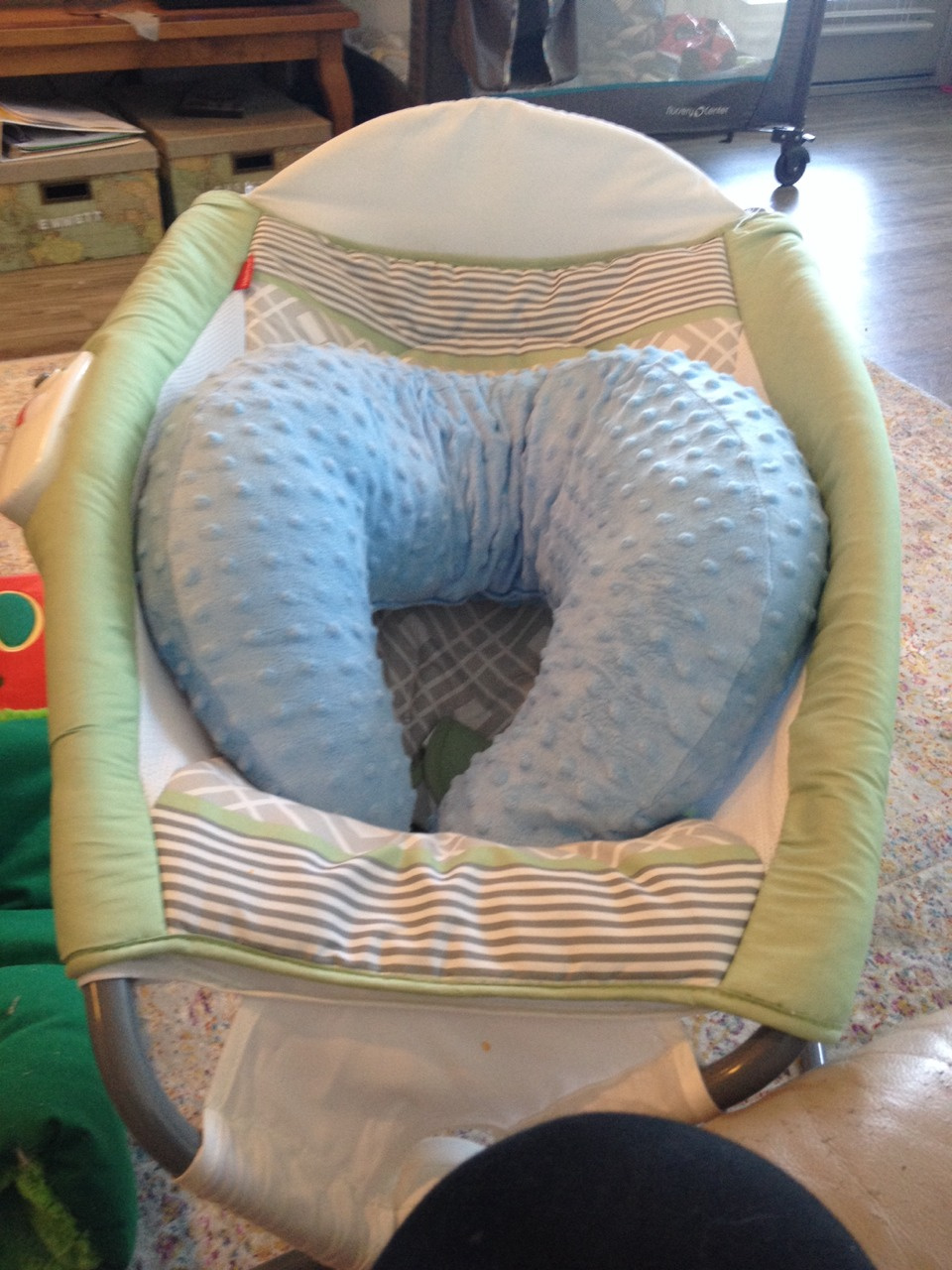 This is his Fisher Price portable sleeper. It has a panel on the side that had a vibration mode (that we don't use because it's over stimulating). Inside it we have place his rounded nursing pillow, which we bought online. It's smaller and softer than a Boppy brand.