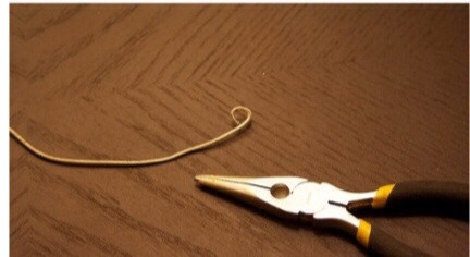 3. Then you going to twist and fold the ends of the hanger on both sides.