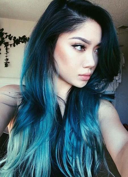 TEAL BLUE TIPS ON LONG HAIR: This woman's color begins with her natural dark hue that fades into two gorgeous shades of blue at the tips. No matter of your race and skin complexion, there is a shade of blue for you.