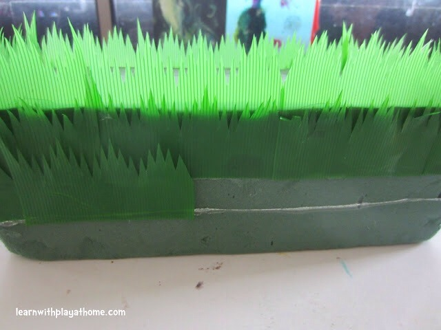 Starting at the top, put a layer of grass dividers around your foam block. Once you have gone all the way around, start a new layer, slightly lower down so that it overlaps the top layer and so on until it is covered.
