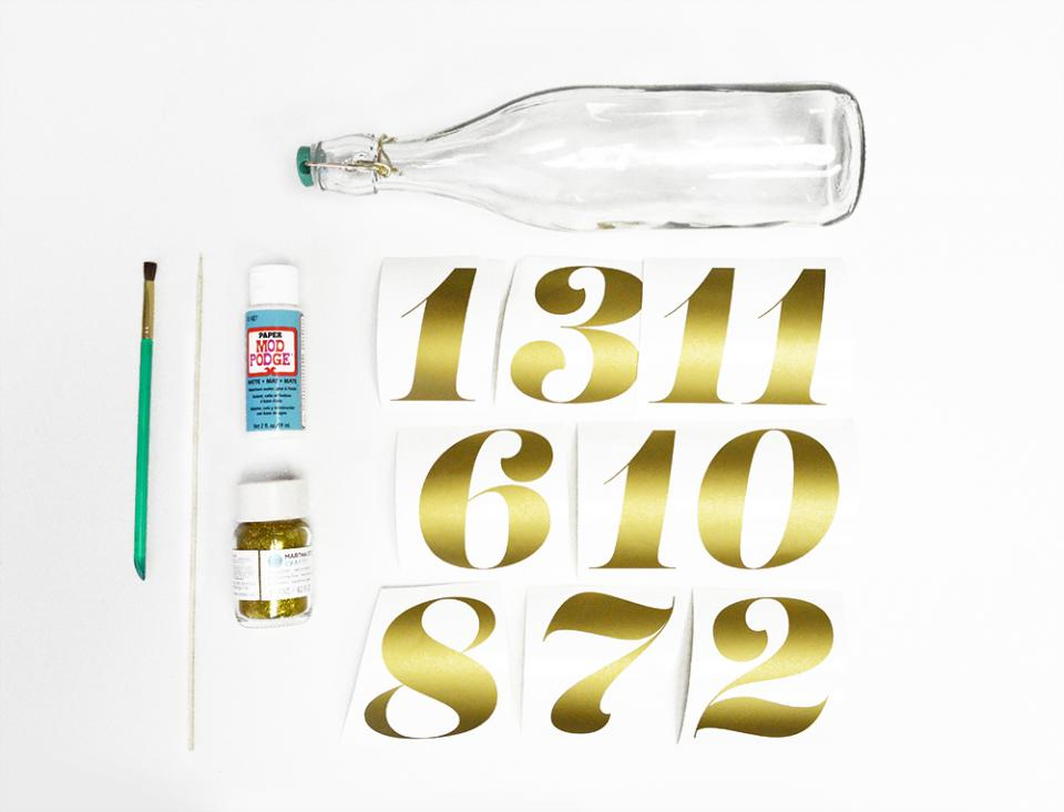 What you'll need:  -Latch-top water bottle (We used ones designed by Oh Joy! for Target) -Mod Podge -Gold glitter -Paintbrush -Stick or toothpick -Gold vinyl -Silhouette Cameo vinyl cutter -Lust Script by Neil Summerour