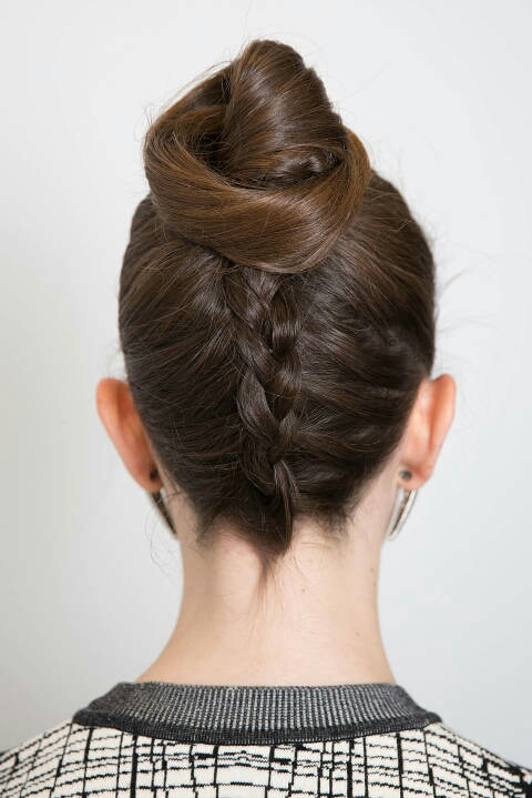 Flip your head over and begin French braiding from the nape of your neck to just before the crown of your head. Secure the braid with a hair tie and wrap the hair around the base of the elastic and pin it into place. Boom: a gorgeous, unconventional bun
