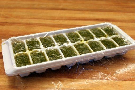 Cover the tray with plastic wrap. Gently tap the plastic down on top of each cube section so it keeps out as much air as possible. Put the tray in the freezer for several hours or overnight so that the cubes freeze completely.