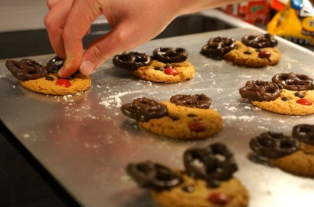 As soon as you take them out of the oven, press the chocolate pretzels on the top. Next press the chocolate chips in for the eyes. Lastly, press in the red M&M for the nose! Warning: be careful! Don't burn yourself!