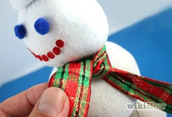 Cut a strip of fabric 3/4 inches to 1 1/4 inches (2-3cm) in width and any desired length. Try to use holiday-themed fabric if you can. Tie the felt around the bottom rubber band as the snowman's scarf.