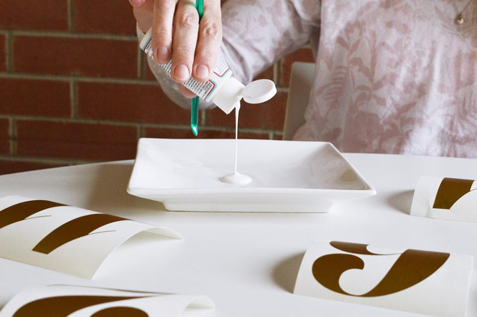 Squeeze a small amount of Mod Podge on a plate or palette and start painting glue on top of the numbers.