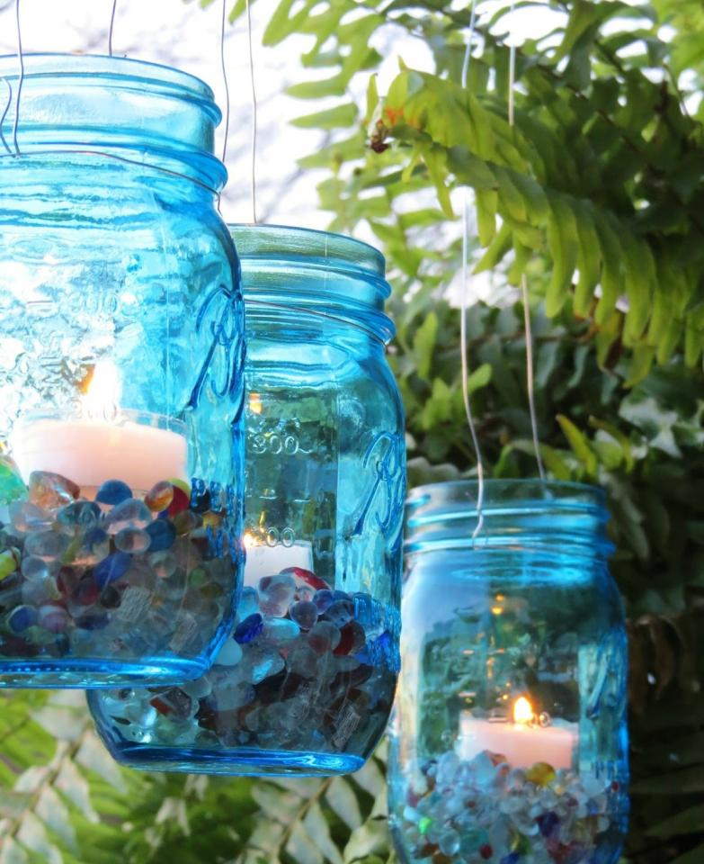 Pour some seaglass stones into a colored Ball jar and place a tealight candle inside, Wrap some wire around the lip of the jar and attach another piece to that to make a handle. Suspend them anywhere you would like, Inside or outdoors!