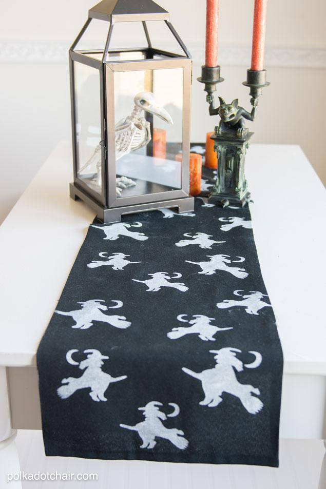 Table Runner: I could not find a solid black table runner. So I purchased a tablecloth that was the length I wanted & cut it to the width I needed (12″). I then just pressed the raw edges under & sealed them with seam tape. NO sewing require ..White Acrylic paint  Small foam roller and paint tray