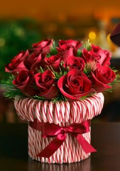 Place the candy canes around a cylindrical vase with a elastic band then place a red ribbon and place roses inside! stunning to bring to someone's house for Christmas!