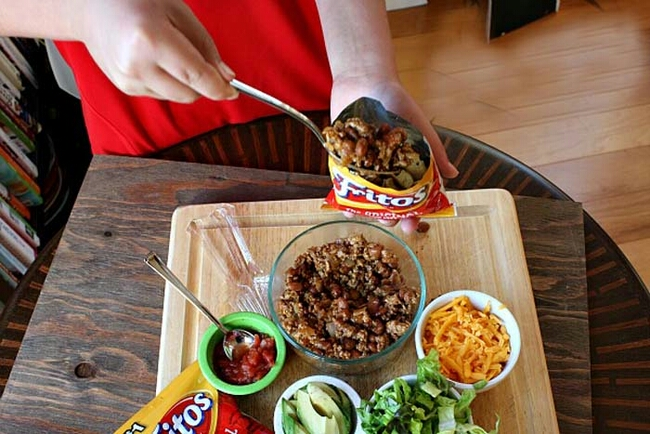 Add taco fixings into a bag of Fritos for a taco salad on the go.