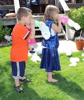 Once the cloth is soaked in solution, blow through the bottle and bubble snakes are formed!