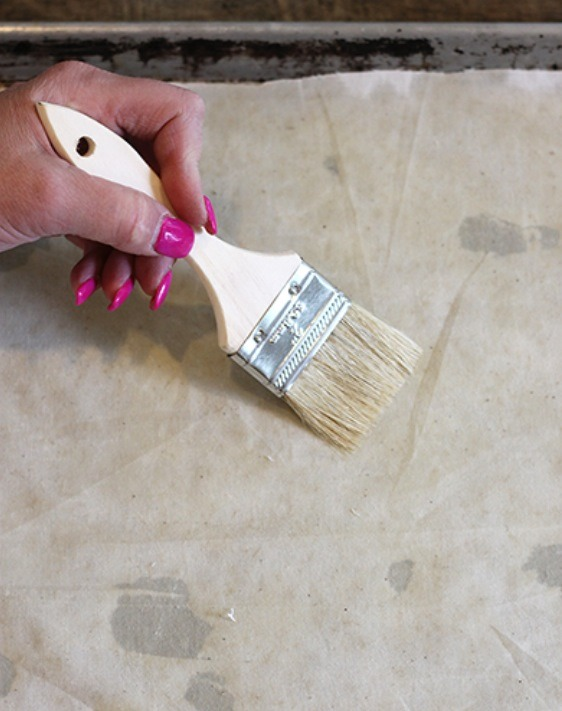 Once the wax is melted, use your paintbrush to spread the beeswax around the fabric, making sure it is evenly covered. Then hang the fabric up somewhere to cool, and it's ready to use!