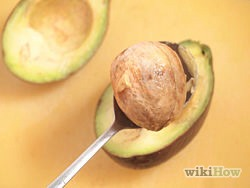 3) Take out the pit, if desired, by gently hacking your knife into the pit and pulling out. You may also use a spoon if the process turns out to be difficult to do it with a knife. Then, when you've removed the pit, you can either discard it or plant an avocado tree.