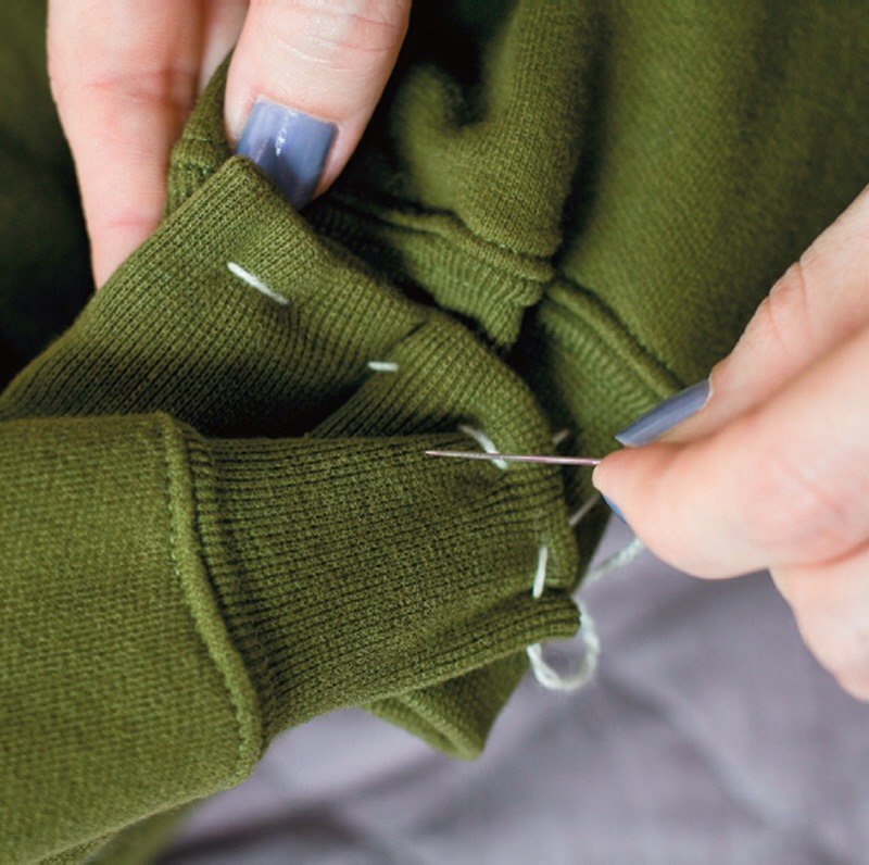 Take one piece of other fabric and put it around the cuffs so that it would cover the sewed part. Sew it with a regular stitch and turn it inwards.