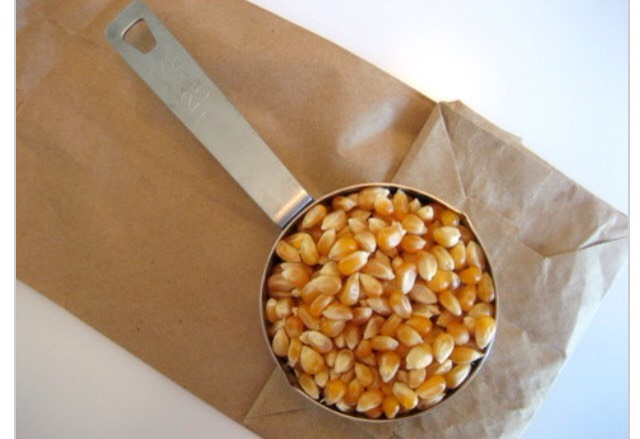 Step Two: Bag your popcorn Add a 1/2 cup scoop of bulk popcorn kernels to your brown paper bag.