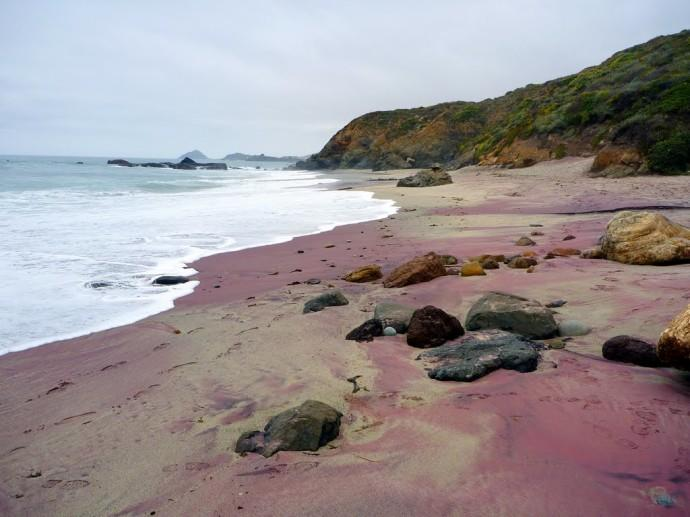 Purple Sand Beach (Pfeiffer Beach) It's located in Big Sur, California, USA. The purple color of its sand comes from its dominant mineral quartz combined with manganese garnet deposits found in the surrounding rocks, which makes it a very attractive tourist destination.